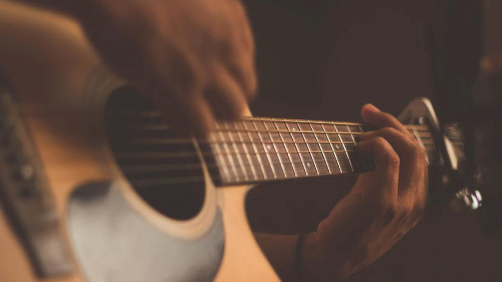 Hands strumming a guitar