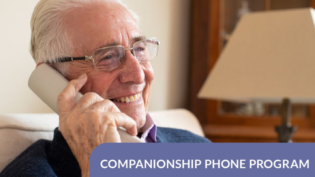 An elderly man smiling on the phone