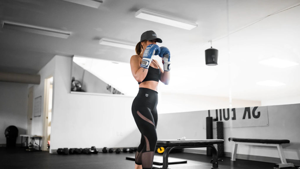 A woman in a ready-stance for kickbox training