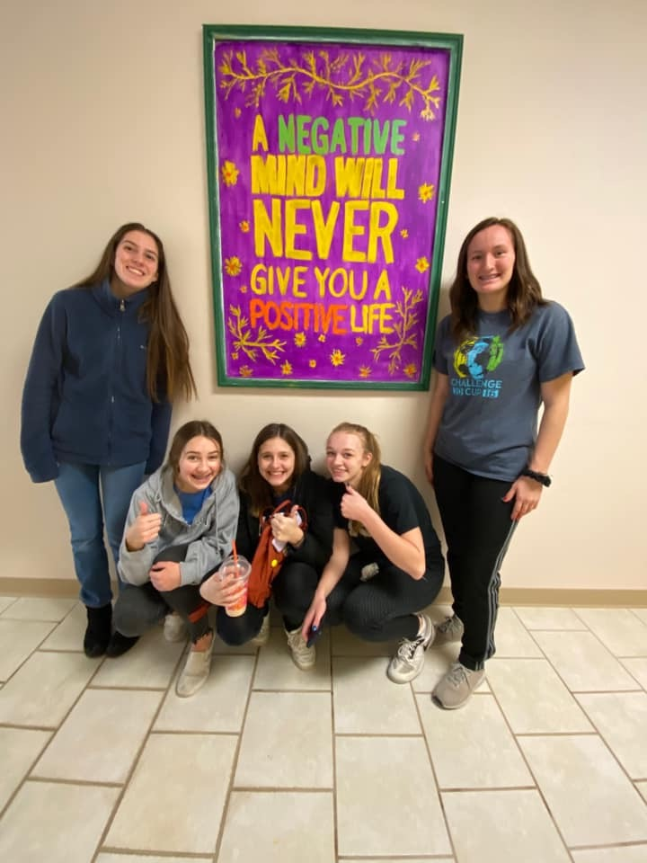 "Students Madison Coats, Myrriam Dhoore, Ella Dubbs, Zoey Loucks, and Joselyn Boyd pose in front of a positive, painted message that says, ""A negative mind will never give you a positive life."""