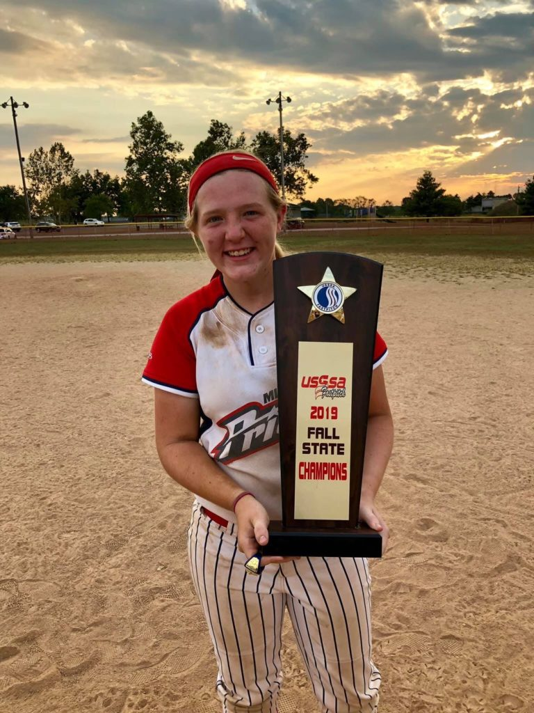 "La Porte High School junior Rebecca Marxman stands on a softball field wearing her softball uniform and holding a trophy that says ""2019 Fall State Champions"""