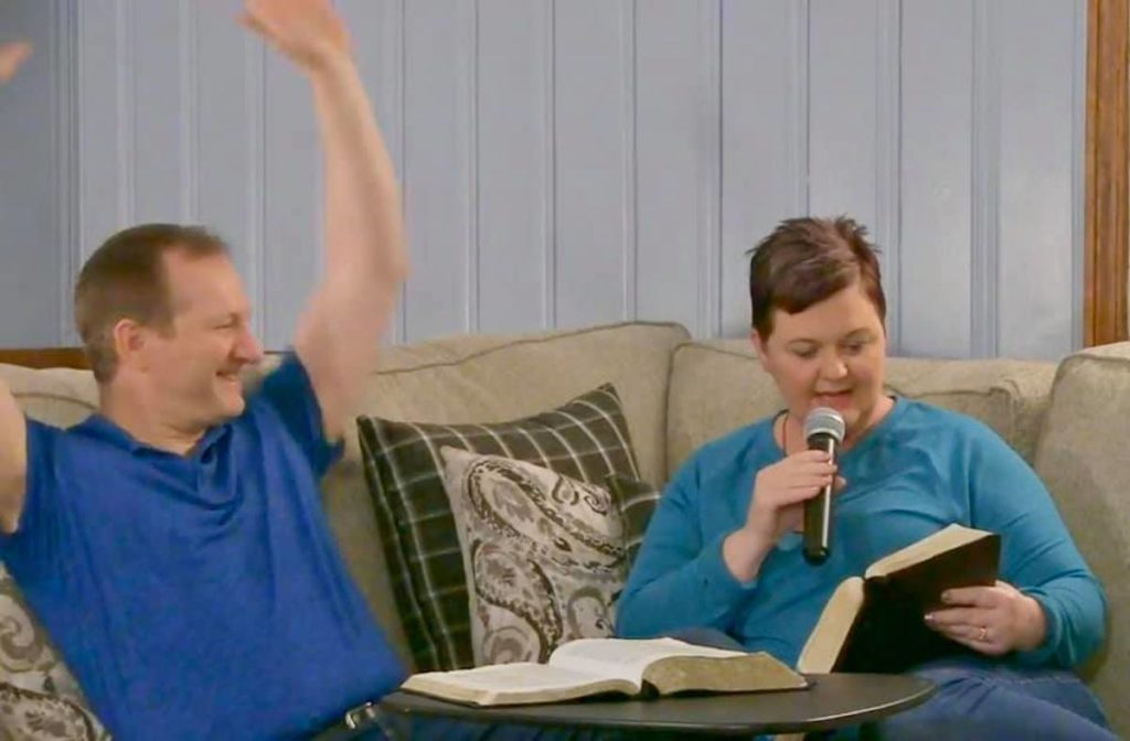 wife and husband on couch reading Bible