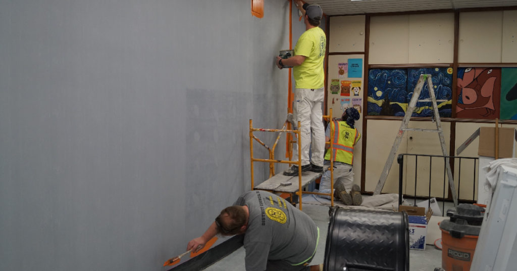Two local union workers begin to paint orange edges on a gray wall in the Lake Station Club of the Boys & Girls Clubs of Greater Northwest Indiana