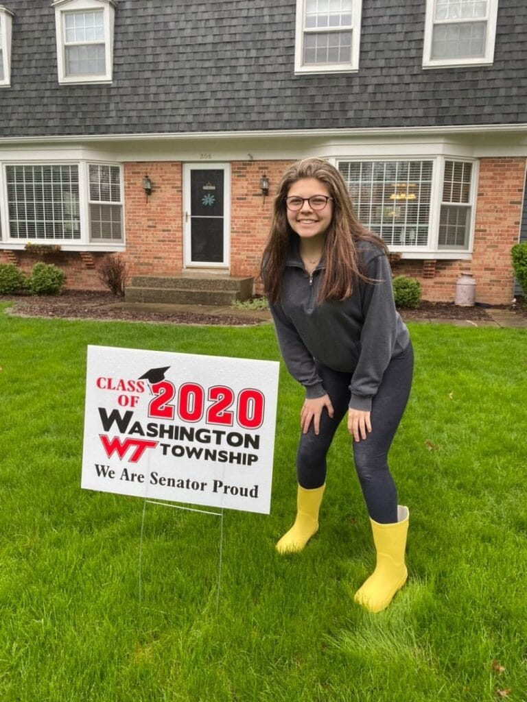 Washington Township High School student stands in yellow rain boots beside senior class sign