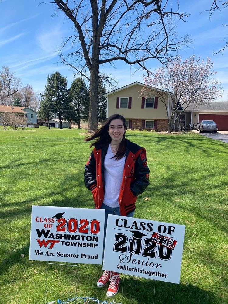 Washington Township High School student stands behind senior class signs