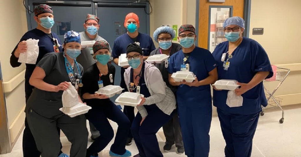 healthcare workers holding donated meals during COVID-19
