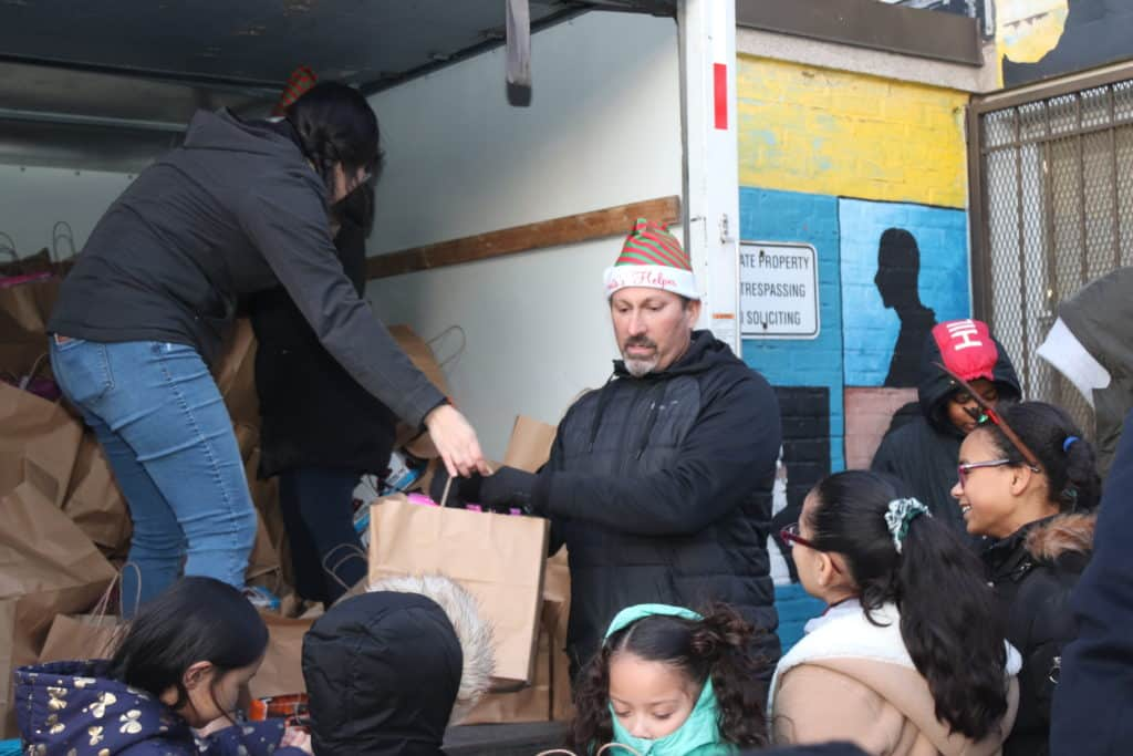 Kevin Rowe wears a Santa hat and hands out gifts to a group of children