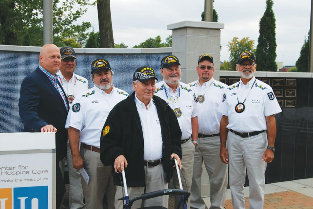 A group of veterans stands before the Center for Hospice Care Veterans Memorial