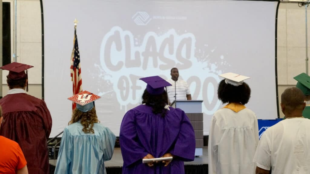 """2 Evans Anthem"": Jamarion Evans of Hammond Boys & Girls Club sings the National Anthem at Boys & Girls Clubs of Greater Northwest Indiana's graduation ceremony as graduates and family look on."