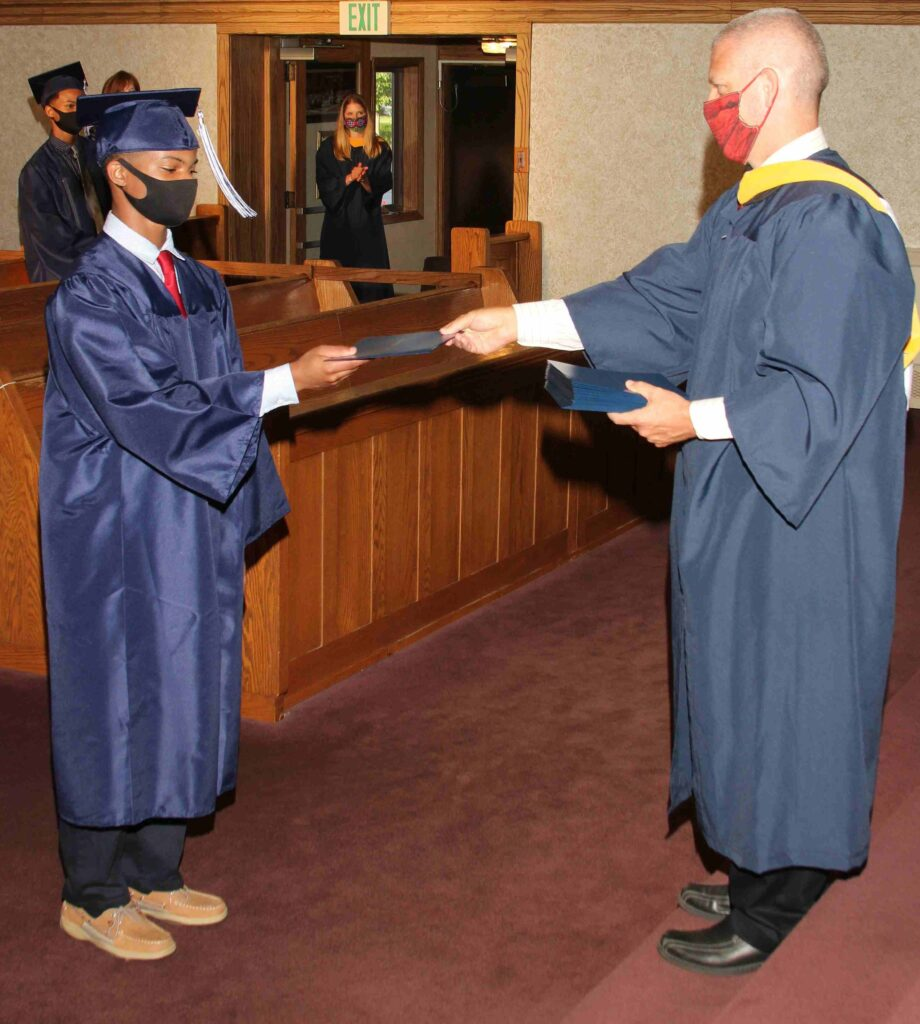 Young boy receives diploma from teacher during graduation ceremony.