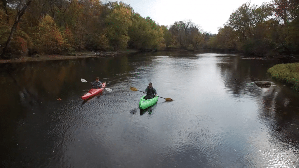 two people in green and red kayaks on a river