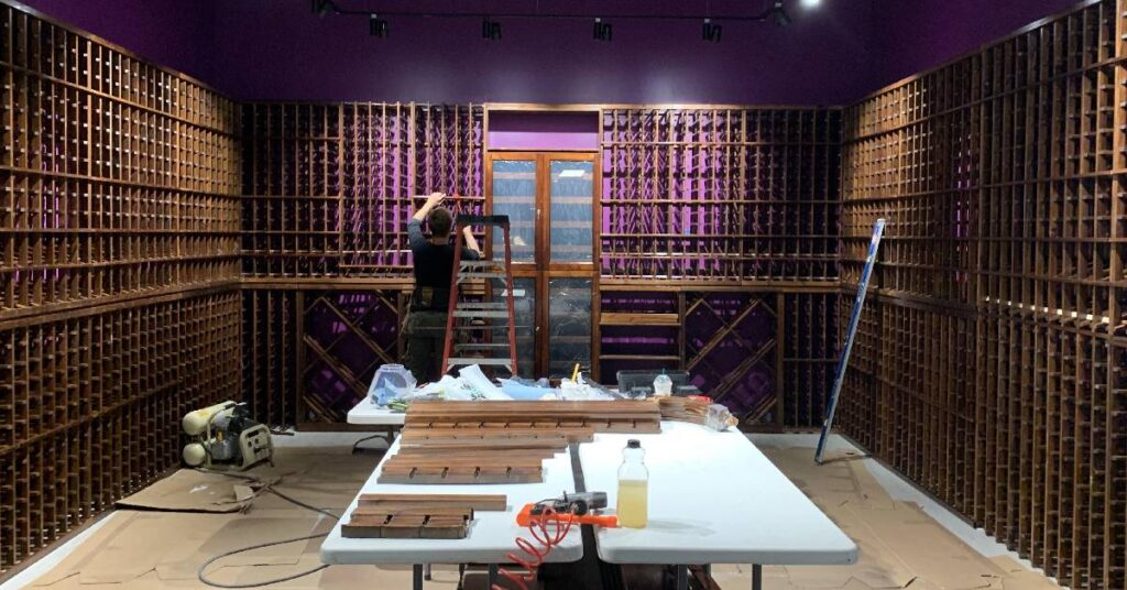 purple room with shelves and a man working