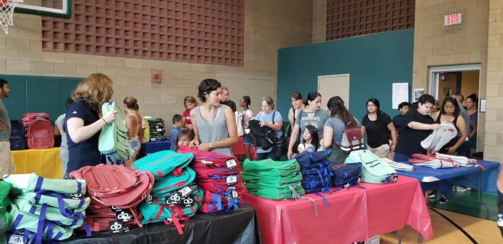 People receiving free backpacks and supplies